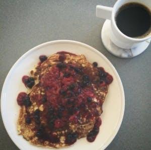 Lite bananpannkaka med frusna bär utan socker med en kopp kaffe. Nyttig och bra frukost.